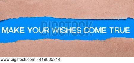 A Strip Of Blue Paper With The Inscription Make Your Wishes Come True Between The Brown Paper. View