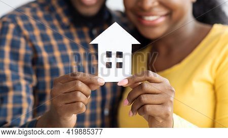 New Home Owners. Happy African American Spouses Holding Paper House Figure
