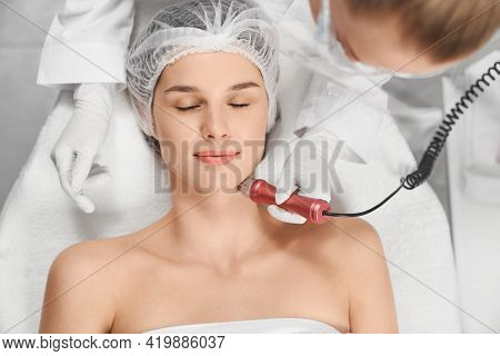 Top View Portrait Of Attractive Young Woman Enjoying Procedure Cleaning Or Massage For Face. Concept