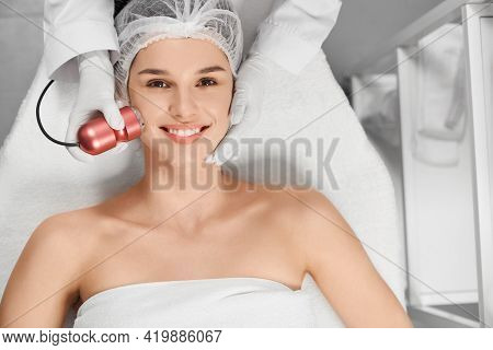 Close Up Portrait Of Satisfied Attractive Woman In Beautician On Procedure With Special Electrical B