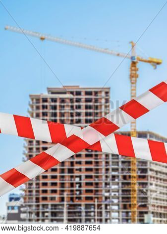 Barrier Prohibition Tape On Blurred Background Of Building Under Construction With High-rise Crane,