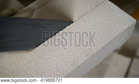 Worker Cutting Construction Blocks Made From Aerated Concrete Using Handsaw. A Worker Cuts An Aerate