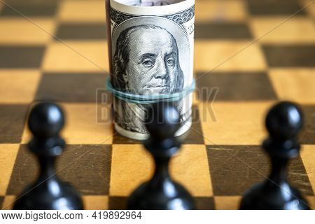 Dollar Bill With Franklin Against Chess Figures, Us Cash On Wooden Chessboard. Finance Symbol And Ch
