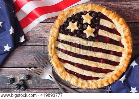 Fourth Of July Patriotic American Flag Pie. Top View Table Scene On A Rustic Wooden Background.