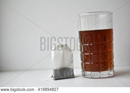 A Glass Cup With Black Tea And A Tea Bag On A White Background