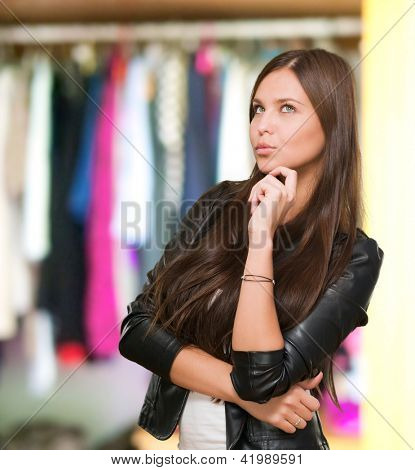 Portrait Of A Young Confused Woman in front of a wardrobe full of clothes