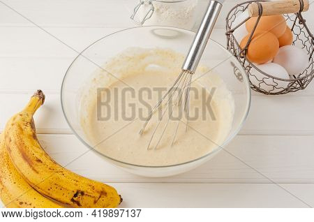 Dough For Cooking Oatmeal Pancakes With Bananas In A Bowl On A White Wooden Background. Recipe Step