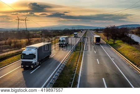 Highway Transit. Convoy Or Caravan Of Transportation Trucks Passing On A Highway At Amazing Sunset.