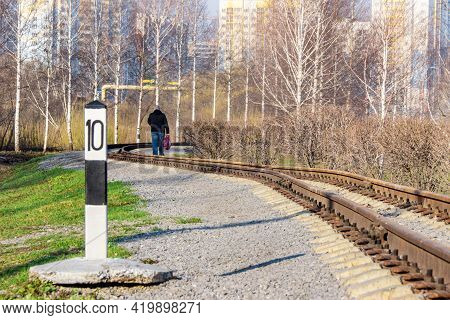 A Winding Narrow-gauge Railway Along Which A Man Is Walking Towards Residential Buildings