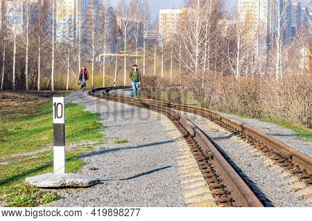 Kemerovo, Russia - 29 April 2021. A Winding Narrow-gauge Railway Along Which People Walk From Reside