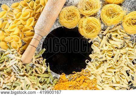 Freshly Cooked Pasta Is Lying On A Dark Surface Dusted With Flour. Italian Pasta. Tagliatelle. Raw P