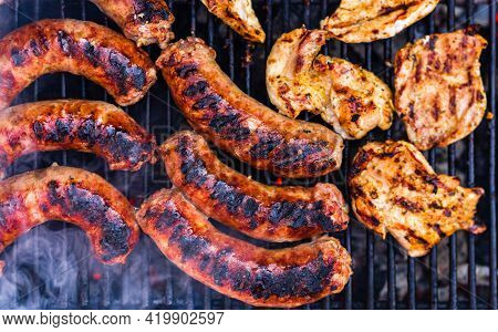 Pork Meat And Sausages Grilled On A Charcoal Barbeque. Top View Of Tasty Barbecue, Food Concept, Foo