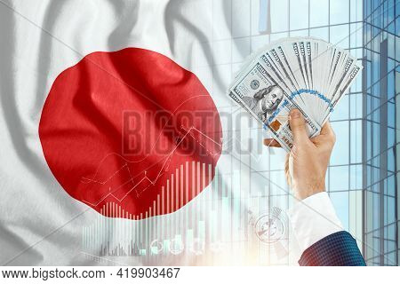 Money In A Man's Hand Against The Background Of The Flag Of Japan. Japanese Income. The Financial Co