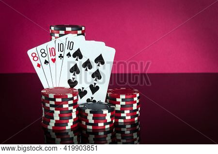 Poker Cards With Full House Or Full Boat Combination. Close-up Of Playing Cards And Chips In Poker C