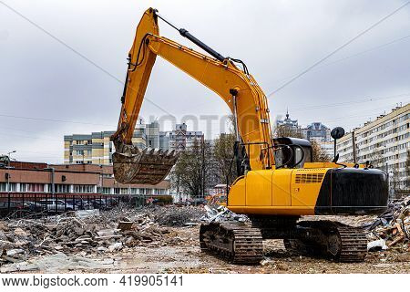 An Excavator Among A Pile Of Garbage After Dismantling An Illegally Constructed Building.