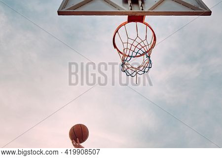 Hand Of Man Throwing Basketball To The Basket Hoop. Bottom Up View Of Basketball Hoop And Ball Again