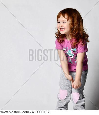 Shy Smiling Cutie Smiling Little Toddler Girl In Sportswear Studio Shot. Child Loudly Laughing. Kid