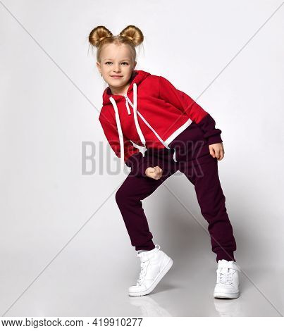 Little Blonde Curly Beautiful Girl In A Red Burgundy Tracksuit And White Sneakers Leans On One Knee
