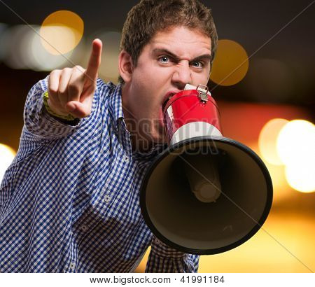 Man Shouting On Megaphone And Pointing Up With His Finger against a city by night