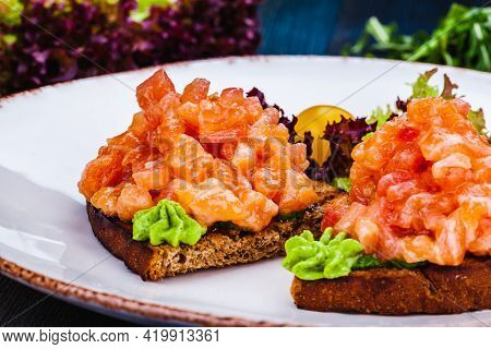 Healthy Toasts With Rye Bread With Salmon, Avocado Mousse, Lettuce On White Plate.