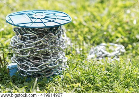 Metal Chromed Chain. The Bay Of The Shining Chain Lies In The Grass. Under The Bright Sun Lies A Coi
