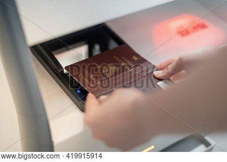 Female Hand Holding Personal Passport Scanning At The Self Service Checkin Counter For Get Boarding