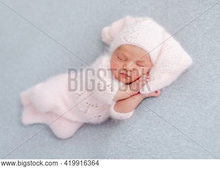 Cute newborn baby girl in knitted hat and costume sleeping on grey background and holding her hands under cheek. Adorable infant child napping during studio photoshoot