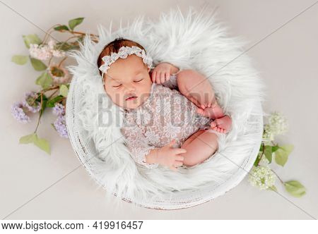 Beautiful newborn baby girl wearing lace costume ana wreath sleeping in basin filled white fur during studio photoshoot. Cute portrait of infant child napping