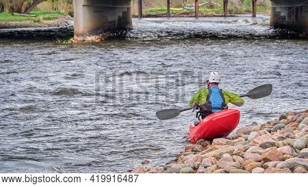 male kayaker wearing drysuit, helmet and life jacket is launching a kayak in the Poudre River Whitewater Park in Fort Collins, Colorado