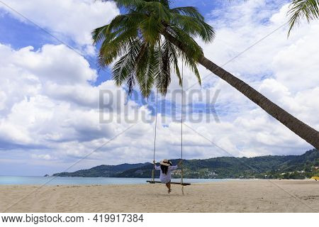 Phuket, Thailand. Tropical Beach Paradise With Beach Swing With Girl In White Shirt. Women Relax On