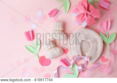 Bonnet And Booties On A Pink Background. Handmade Clothes For A Newborn, Decorative Paper Flowers. N
