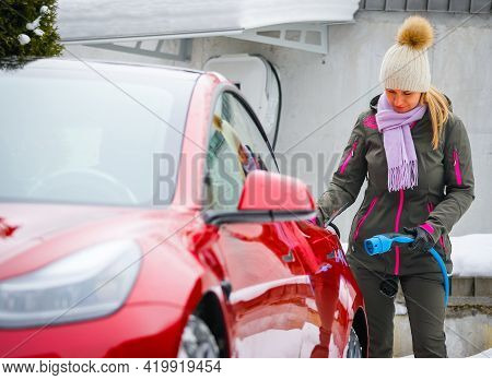 Stylish Girl Stands Near The Electric Car And Waits For The Car To Charge. Connecting The Plug Of Th