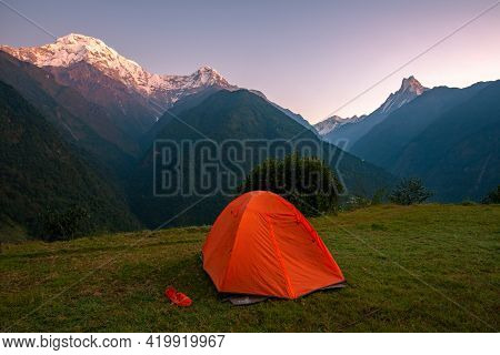 An Orange Tent With Beautiful View Of Annapurna Mountains Range In Annapurna Sanctuary, Nepal At Daw