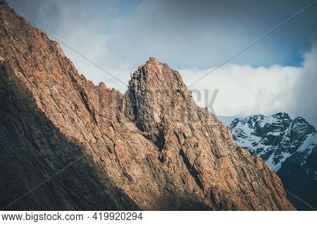 Awesome Landscape With Sunlit Rocky Pinnacle On Background Of High Snowy Mountains In Low Clouds. At