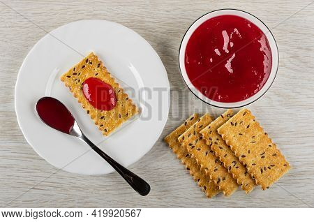 Teaspoon With Jam, Cracker With Flax Seeds Poured Cherry Jam In White Plate, Bowl With Jam And Few C