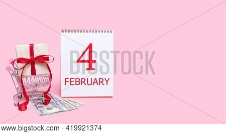 4th Day Of February. A Gift Box In A Shopping Trolley, Dollars And A Calendar With The Date Of 4 Feb