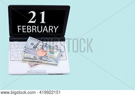 21st Day Of February. Laptop With The Date Of 21 February And Cryptocurrency Bitcoin, Dollars On A B