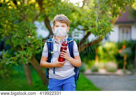 Happy Little Kid Boy With Medical Mask And Satchel. Schoolkid On Way To School. Healthy Child Outdoo