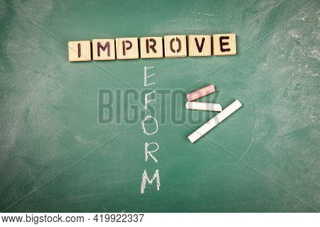 Improve And Reform Concept. Wooden Alphabet Letters On A Green Chalk Board