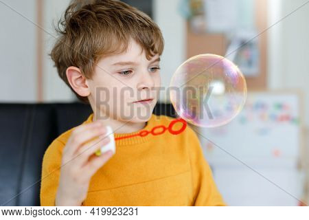 Happy Little School Boy Playing With Soap Bubbles At Home. Kid Having Fun. Child Playing At School,