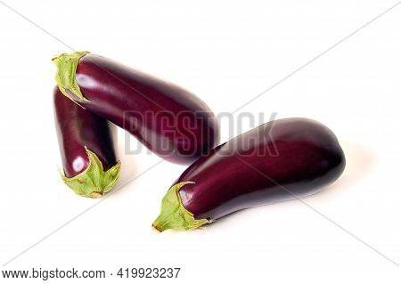 Three Eggplants With A Green Sepal. Isolate On White Background