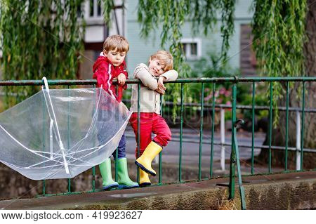 Two Little Boys, Best Friends And Siblings Walking With Big Umbrella Outdoors On Rainy Day. Preschoo