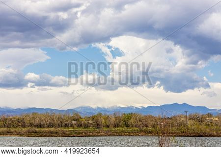 Colorado Landscape Near Brighton, Colorado. Small Pond And Grass With The Long Peek View In The Dist