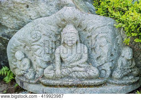 Miniature Sitting Buddha In Front Of Boulder In Garden.