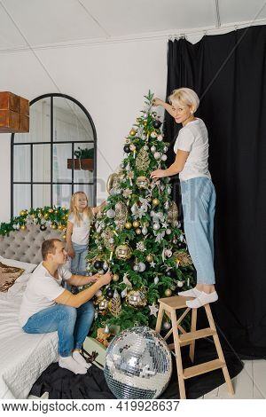 Beautiful Young Happy Family Decorate The Christmas Tree.