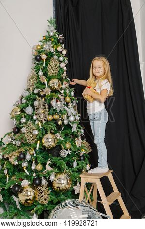 Beautiful Little Girl Decorates A Christmas Tree While Standing On The Stairs.