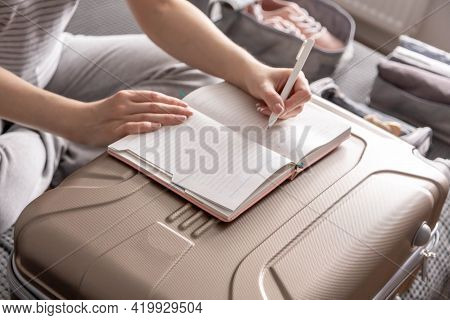 Closeup Female Hands Writing Paper Notes Making List Of Necessary Things To Travel Trip Vacation