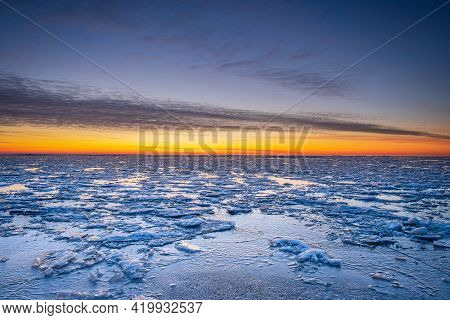 Winter Landscape In Beach, Coastline With Cracked Ice, Snow And Opened Sea Water On Sunset.