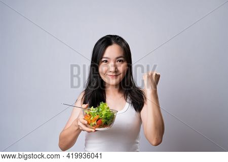 Asian Woman Eating Salad Isolated Over White Background.