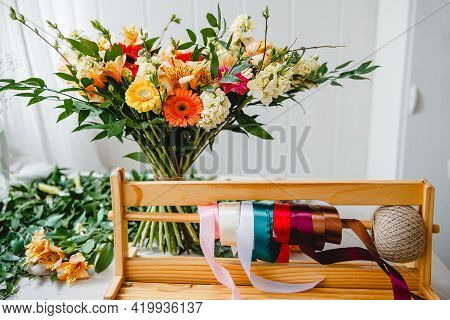 A Lush Bouquet In The Style Of Boho Stands On The Florists Desk Behind A Wooden Stand With Colorful